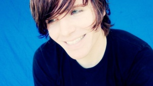 Onision in front of his blue screen, smiling.